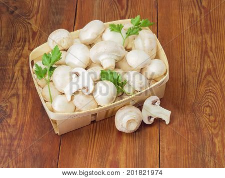 Fresh cultivated button mushrooms and twigs of parsley in the wooden basket one whole mushroom and mushroom cut in half separately beside on an old wooden surface