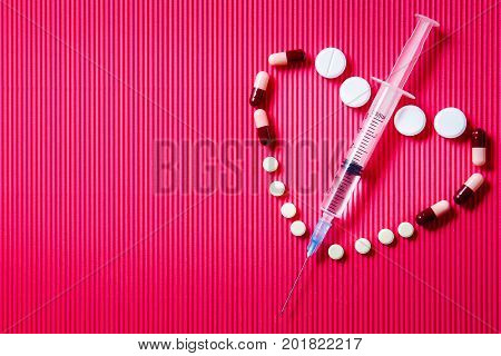 Pills and syringe. Pills and syringe on red background in shape of heart. Copy space