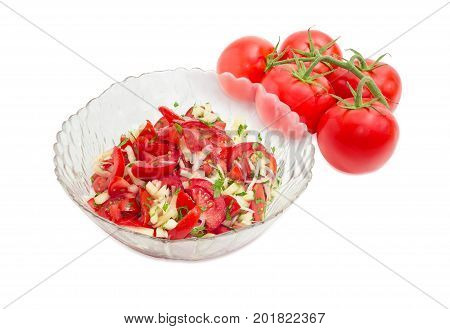 Vegetable salad of the fresh sliced tomatoes white bell pepper onion and potherb in a glass salad bowl against of the cluster of fresh tomatoes on a white background