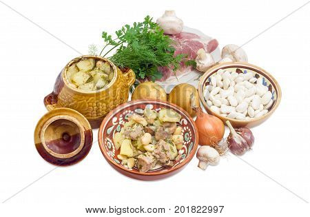 Ukrainian version of the dish Chanakhi in a clay bowl - potatoes with meat mushrooms and haricot beans roasted in a clay pot and ingredients for its preparation on a white background