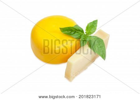Piece of the parmesan cheese and small wheel of firm goat cheese with twig of green basil on a white background