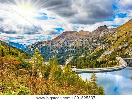 Mountain Lake Lago di Fedaia, Dolomites. Powerful dam blocked the lake. The concept of ecological and extreme tourism. A cool autumn day at Mount Marmolada