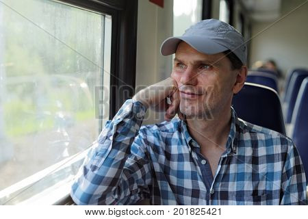 Mature man looking through the window in a commuter train