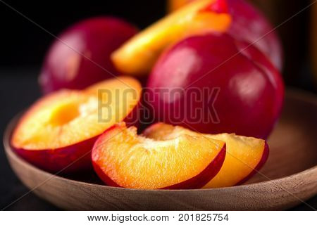 The red cut fruit on a wooden dish. Pieces of a nectarine of red color dark background rural style close up selective focus