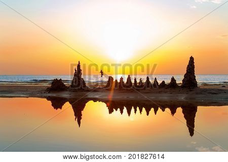 Beach with sandcastles on spectacular Baltic sea sunset background in Latvia. Vibrant multicolored summertime outdoors horizontal image. Copy space.
