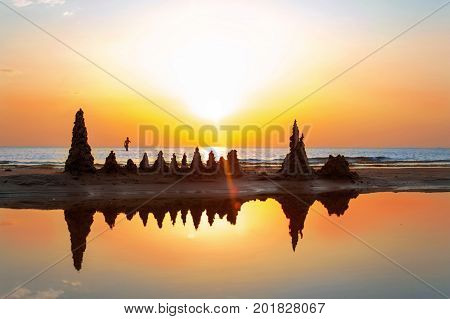 Beach with sandcastles on spectacular Baltic sea sunset background in Latvia. Vibrant multicolored summertime outdoors horizontal image with filter.