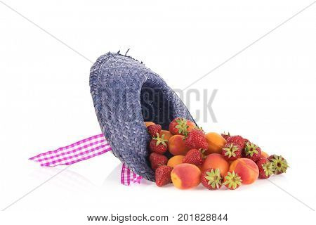 Blue straw summer hat full with fresh abricots and strawberries