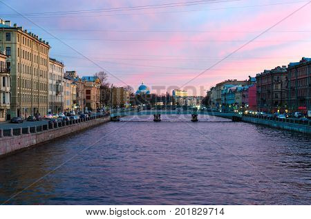 SAINT PETERSBURG RUSSIA - MAY 1 2017: Evening view of embankment of Fontanka River. On background - Cathedral of Holy Life-Giving Trinity of Life Guards Izmailovsky Regiment (Trinity-Izmaylovsky Cathedral Trinity Cathedral)