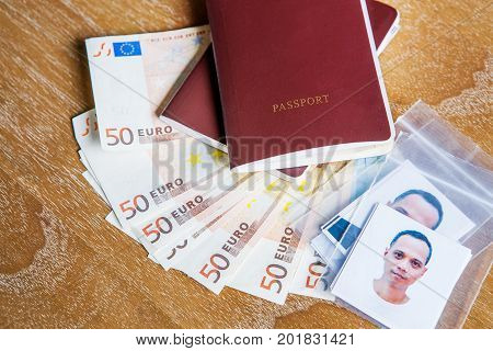 red cover passport book face of asian man with fifty euro bank note on wood table
