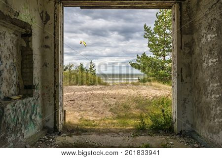 Coastal landscape with dune, Baltic Sea and pine trees seeing through a frame of old destroyed building