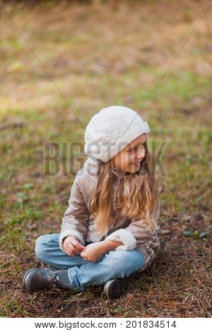 portrait of a beautiful little girl in an autumn park. Blond girl in white beret