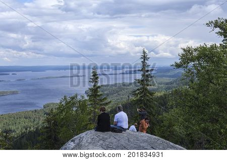 UKKO-KOLI HILL, FINLAND ON JULY 05. View of lake Pielinen from a rock, cliff on July 05, 2017 in Ukko-Koli Hill, Finland. Unidentified people at the outlook. Editorial use.