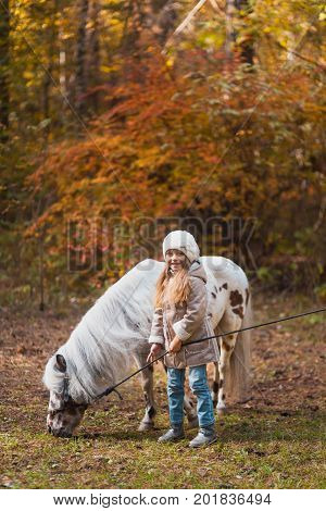 Little Cute Girl Walking With A Pony In The Autumn Forest