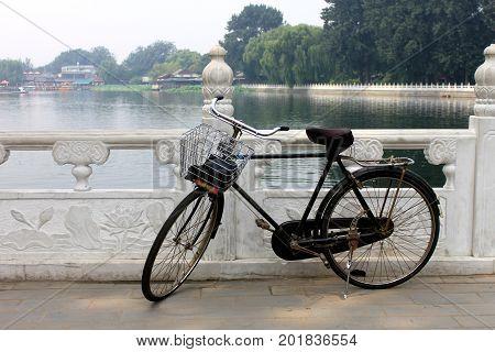 The Old Unused Bike Lay On The Railing Of Houhai Lake Park, Beijing