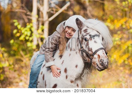 Little Beautiful Girl Sitting On A Pony In The Autumn Park