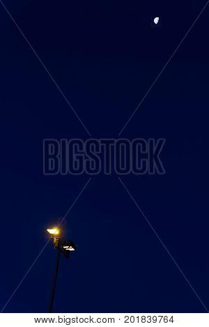 moon above street lamp at darken night