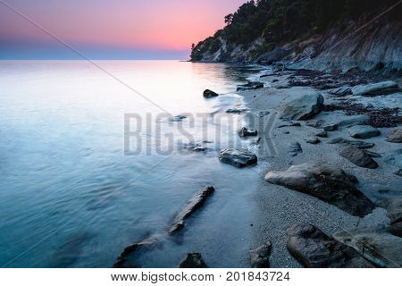 Long exposure of a dreamy and colorful sunset on a rocky beach in Chalkidiki Greece