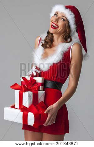 Smiling woman dressed in pin-up dress santa claus style holding christmas gift boxes