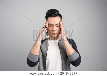 Young Sad Thoughful Asian Man Having Headache After Work.