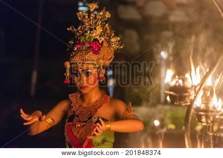 Ubud, Indonesia - August 8, 2016: Beautiful balinese woman dances during a traditional Kecak Fire Dance ceremony in Hindu temple.
