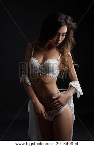Slim tattooed brunette with long locks topless posing in white lace lingerie and dressing gown draped over her heaps against black background