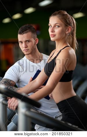 Closeup of blonde female working out on elliptical machine with the assistance of personal trainer. Healthy lifestyle, fitness and sports concept. Focus on man.