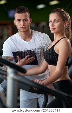 Closeup of blonde female working out on elliptical machine with the assistance of personal trainer. Healthy lifestyle, fitness and sports concept. Selective focus