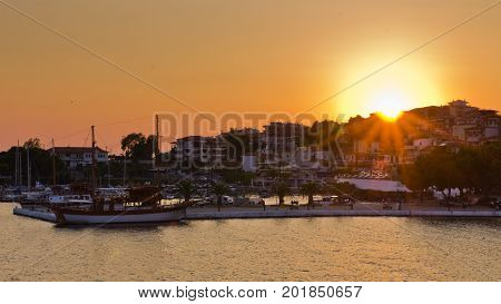 Ships in a harbor of Neos Marmaros at sunset in Sithonia, Greece