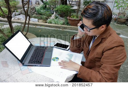 Wide angle shot of handsome young businessman is talking on the phone for his work with laptop and paperwork at public outdoor.