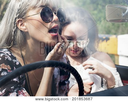Woman Sitting in a Car Putting Lipstick on Lips with Rear Mirror