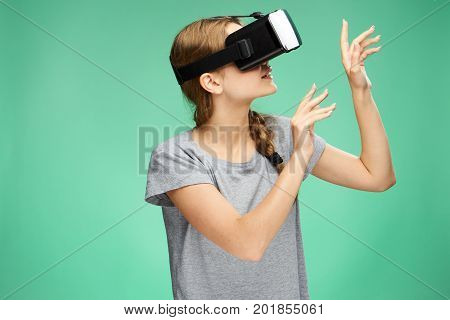 Beautiful young woman on a green background with virtual reality glasses.