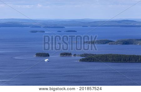 View of a vast lake, islands and islets. White ship approaching, woodland up North.