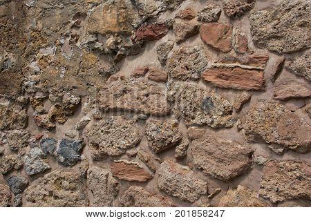 Ancient stone wall. Masonry of old stones and bricks. Beautiful unusual background.