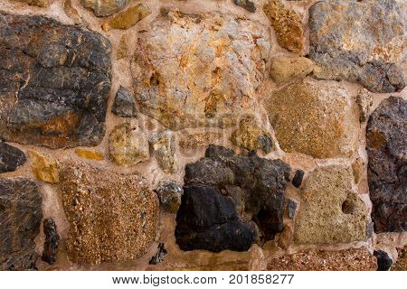 Ancient stone wall of an ancient fortress. Masonry of old stones and bricks. Beautiful unusual background.