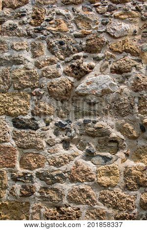 Ancient stone wall of a sea fortress. Masonry of old stones and bricks. Beautiful unusual background.
