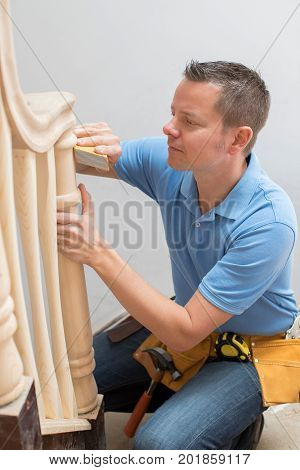 Carpenter Using Sandpaper On Bannister In Home