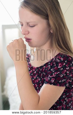 Girl Suffering With Cough Sits On Bed At Home