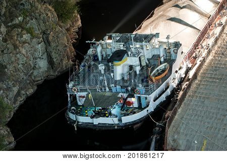 Cargo barge runs aground near the rocky shores of the river at night. Rescue vessels arrived on the scene.