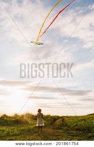 Anonymous girl playing with colorful kite flying in air on background of green field.