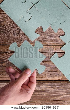 Incomplete puzzles lying on wooden rustic boards. Conceptual of innovation, solution finding and integration. Hand with puzzle piece