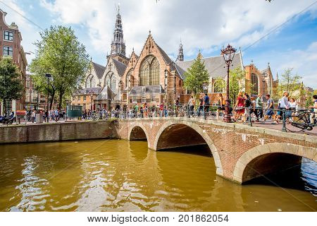 AMSTERDAM, NETHERLANDS - August 07, 2017: View on the water channel with the Old church and tourists on the street at the red light district in Amsterdam