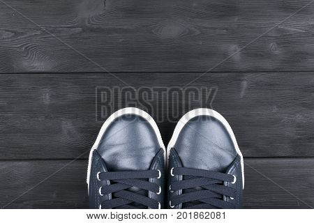 Overhead view of shoes on black wooden floor. Shoes on a wooden background. Sneakers on a wooden floor. Sport fitness shoes footwear and objects concept