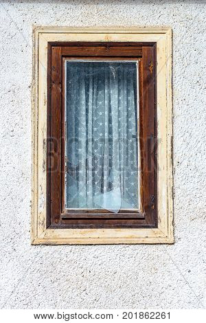 A Destroyed window pane in a wood window at the village