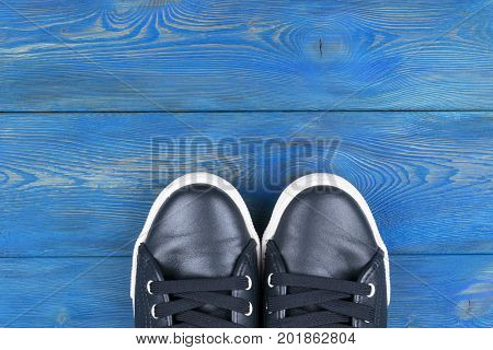 Overhead view of shoes on blue wooden floor. Shoes on a wooden background. Sneakers on a wooden floor. Sport fitness shoes footwear and objects concept
