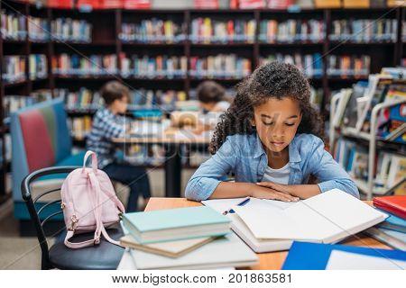 african american schoolgirl reading book in library
