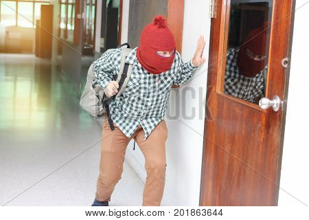 Masked burglar escaping after sneaking into the house. Crime concept