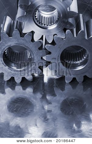 three cogs reflecting in stainless-steel