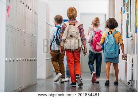 back view of kids going in class through school corridor