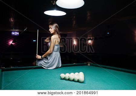 Portrait Of An Attractive Young Woman In Dress Sitting On The Pool Table And Holding A Cue.