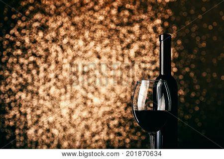 Wine In Glass Near Bottle On Sparkling Metallic Background